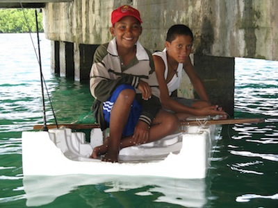 Boys fishing under the town wharf on a piece of styrafoam that blew in after Hurricane Ida.
