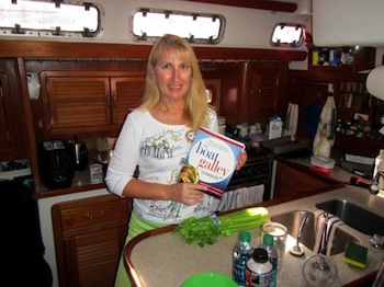 Tammy Swart aboard Dos Libres, with her copy of The Boat Galley Cookbook