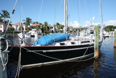 The dinghy spends the summer months upside down and partially deflated on the foredeck covered with a blue dinghy cover.