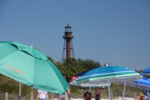 Surrounded by beach umbrellas, the Sanibel Lighthouse is a popular beach location on the southern tip of Sanibel Island.