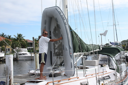 The DInghy is vertical against the mast and David is positioning the kayak holders to hold the stern in place.  Look at the base of the transom of the dinghy.