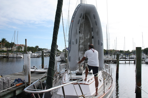 David maneuvers the dinghy into place on the foredeck - it's still vertical.