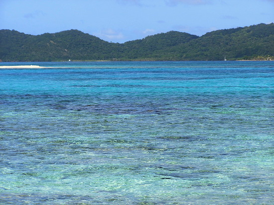 See the tiny white spec far right in the photo - that's Winterlude anchored in the reef strewn waters by Barbareta, Bay Islands, Honduras.