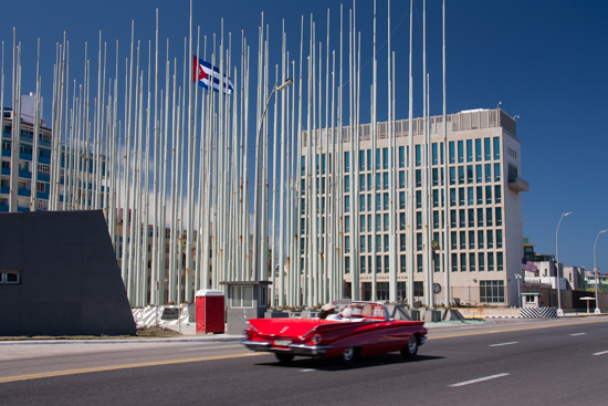 Convertible flying down the Malecon in front of the US Embassy. Notice the US Flag is at half mast in honor of Nancy Reagan.