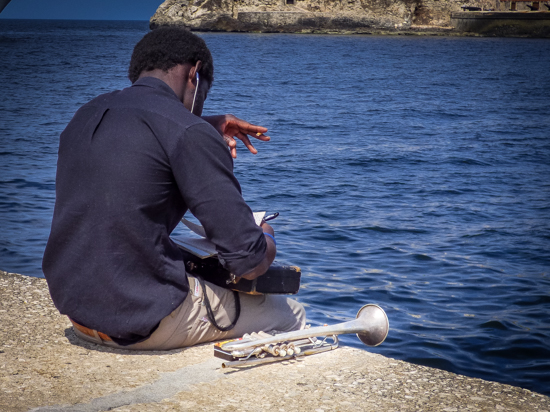 Writing music while waitng until time to perform, this trumpet player enjoys the entrance to Havana Harbor.
